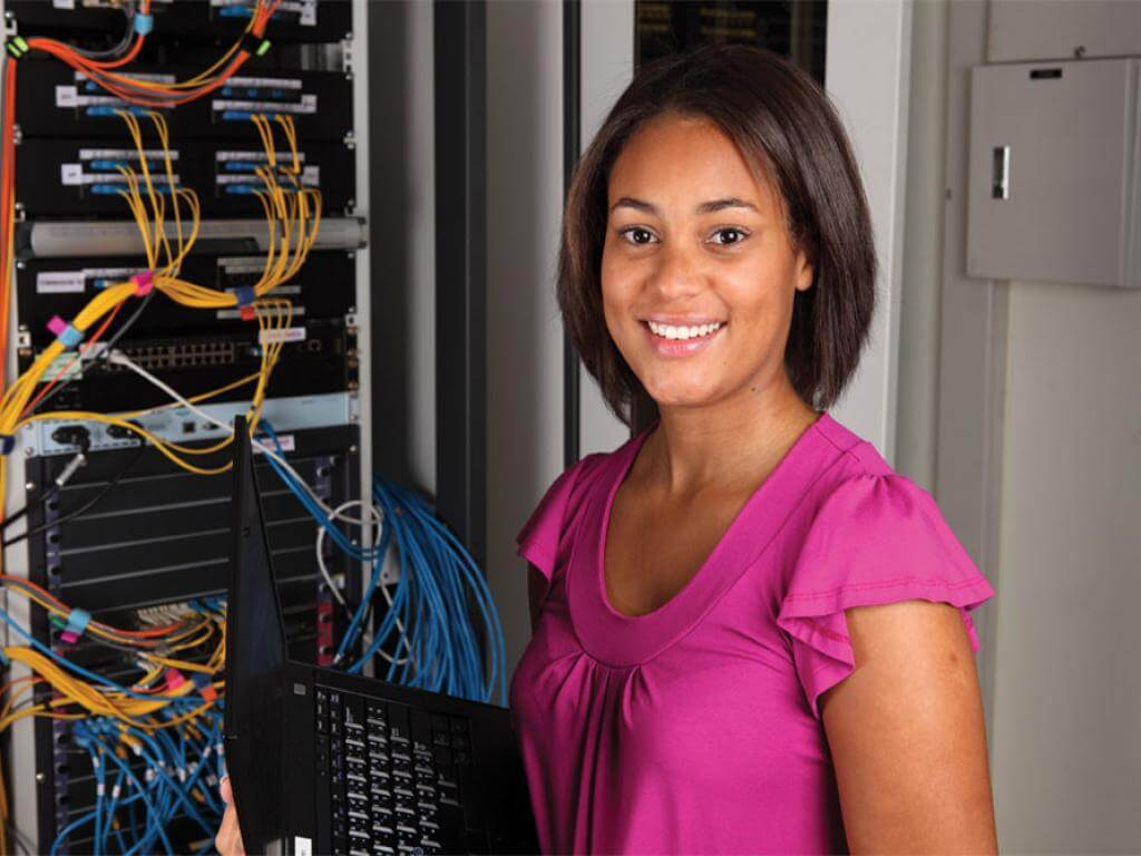 woman standing in front of computer network wiring panel