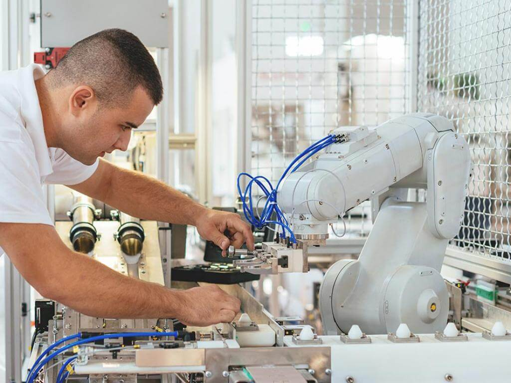 Engineer repairing a robotic arm in a manufacturing setting
