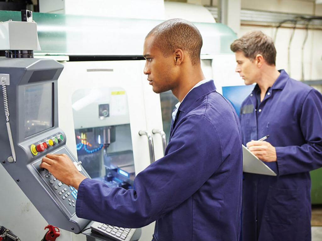 Industrial engineers monitor a manufacturing system