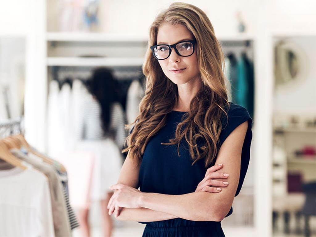 Female fashion merchandiser poses for a portrait in a clothing shop.