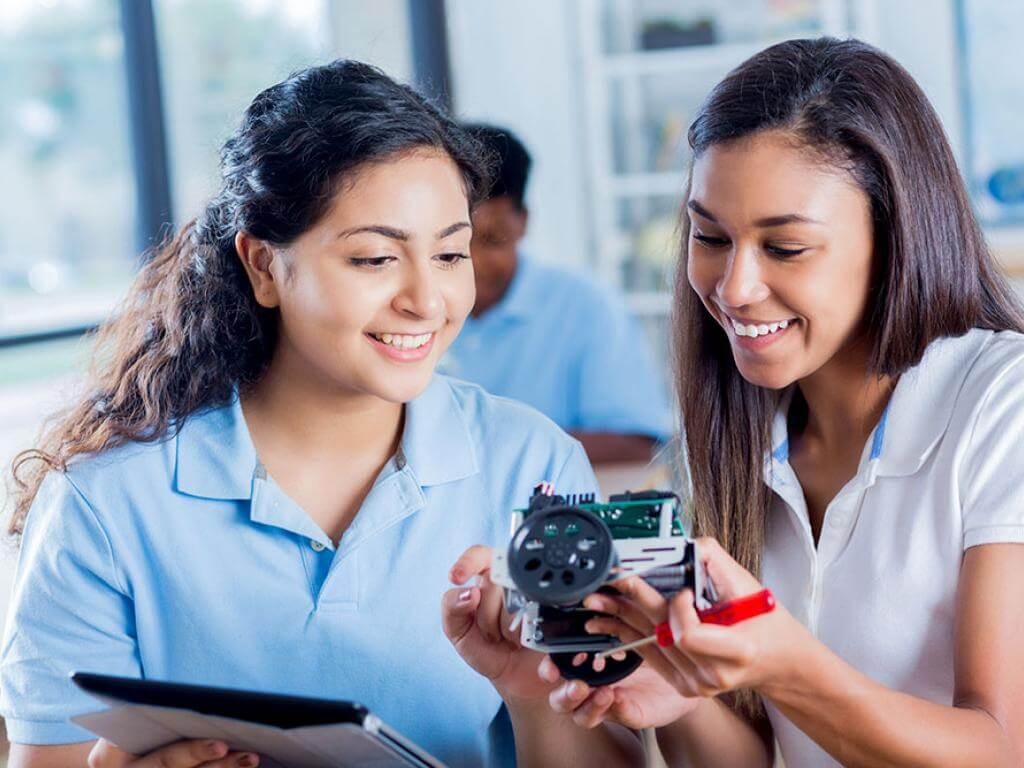 Two smiling female high school students examine a robotic component