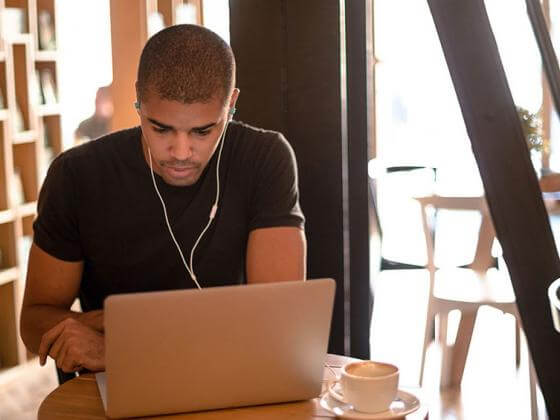 Man wearing earbuds and studying at laptop