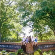 graduates sitting on Old Dominion University sign